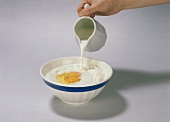 Pouring milk on to flour and egg yolk in dish