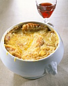 Onion soup in soup tureen; red wine glass