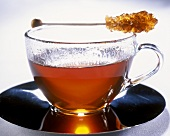 Tea in glass cup with sugar stick