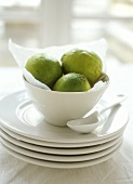 Limes in white bowl on pile of plates