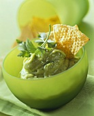 Avocado mousse with nachos (taco chips) in green bowl