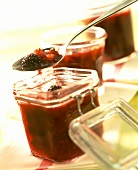 Blackberry chutney with tomatoes in jars and on spoon