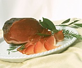 Raw ham garnished with rosemary and bay leaf