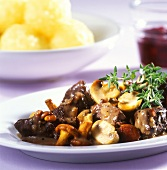 Game goulash with mushrooms, potato dumplings behind