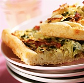 Spring onion tart with bacon on pile of plates