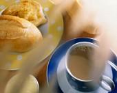 Brazilian breakfast with white coffee, roll, butter