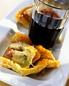 Tasty apple tart with blue cheese; red wine glass