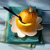 Ausgehöhlter Kürbis mit Löffel für Kürbissuppe zu Halloween