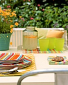 Summer table in garden with coloured plates & lemonade