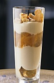 Coupe caramel with cream and biscuit in glass