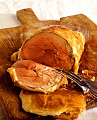 Boned leg of lamb in puff pastry on wooden chopping board