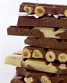 Pile of pieces of white and dark chocolate with hazelnuts