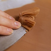 Scraping chocolate from a baking tray (making chocolate fans)