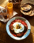 Tunisian rissoles with tomatoes and fried egg; flatbread