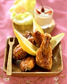 Chicken wings with lemon wedges and peanut dip