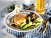 Pork chop with cheese crust and salad; beer