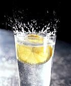 Zitronenscheibe fällt spritzend in Glas Mineralwasser
