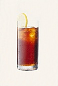 Cola in glass with drops of water, ice cubes & lemon