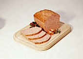 Coarse meatloaf, a slice cut, on wooden chopping board