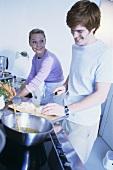 Junges Paar in Küche beim Zwiebelschneiden und Abwaschen