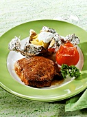 Rump steak with baked potato and grilled tomato