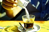 Tipping sugar into coffee