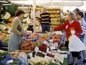 Woman at market stall pointing to vegetables