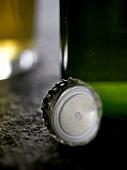 Crown cap beside wine bottle