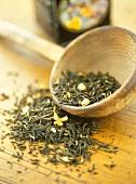 Grüner Tee auf Holzuntergrund und im Schälchen