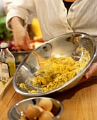 Mixing polenta with olive oil in a dish