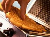 Hand taking freshly baked waffle out of waffle iron