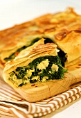 Cheese and spinach pie on chopping board