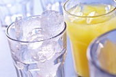 Ice cubes in glass; orange juice