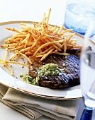 Grilled steak with parsley butter and chips