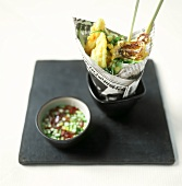 Asian cuttlefish kebabs in newspaper; spicy dip
