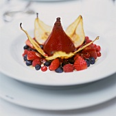 Poached red wine pear with pear crisps and berries