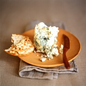 Stilton and cracker on wooden plate