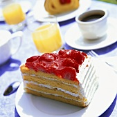 Piece of strawberry gateau, coffee & orange juice on table