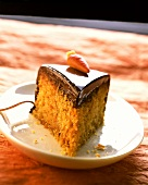 Piece of carrot cake with chocolate icing & marzipan carrot