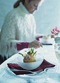 Shrimps-Möhren-Cocktail auf Tisch; Frau im Hintergrund
