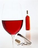 Glass of red wine in front of bottle; cork; corkscrew