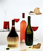 Red wine bottles and glasses, rosé bottle, cheese and olives