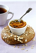 Orange marmalade in bowl on oat bread; tea