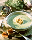 Artichoke soup with herbs and bread cubes