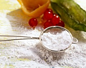 Icing sugar in sieve and fruit