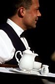 Waiter serving tray of coffee and milk