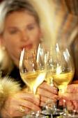 Elegant people clinking white wine glasses