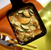 Courgettes with cheese in raclette pan
