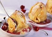 Marzipanäpfel mit Kirschsauce (mit Löffel angestochen)