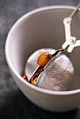 Tea strainer with fruit tea in tea bowl